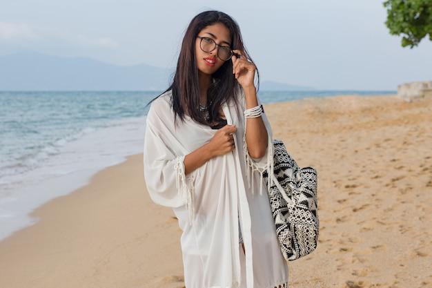 열 대 해변에서 산책하는 흰 드레스에 여행자 귀여운 아시아 여자. 휴가 즐기는 예쁜 여자
