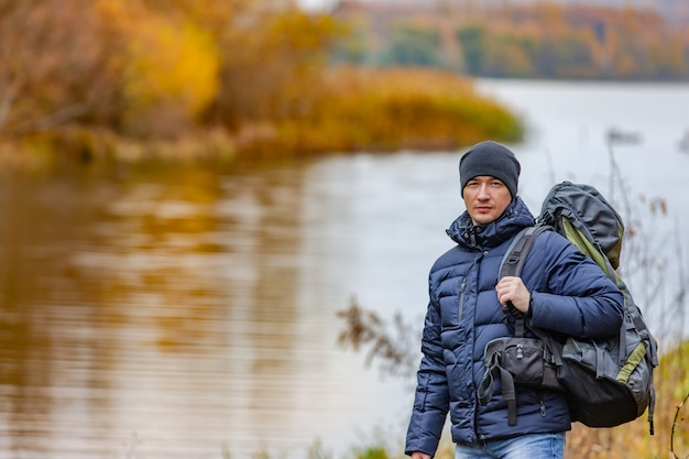 Traveler dressed in warm clothes stands near the river of the autumn landscape