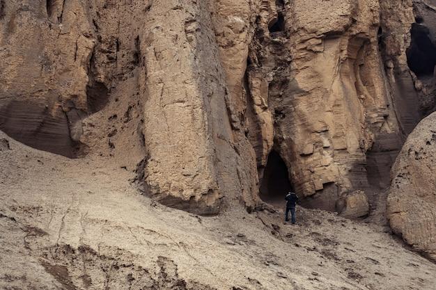 Путешественник изучает пещеры в горной местности