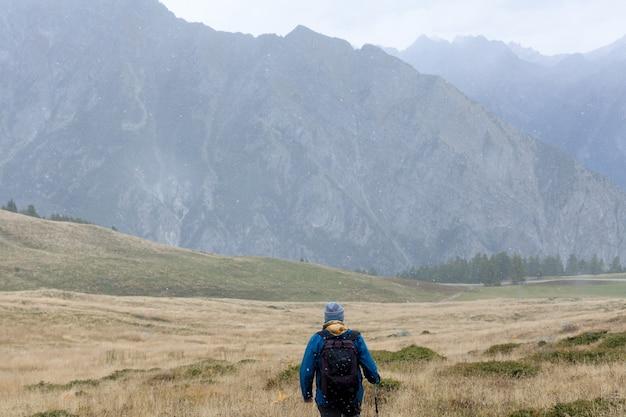 배낭을 메고 혼자 산을 탐험하는 여행자 알파인 산 복사 공간이 있는 후면 보기