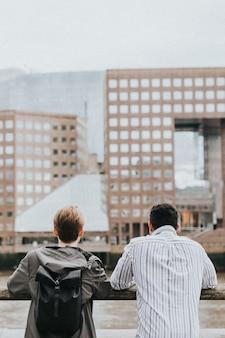 橋からロンドンのスカイラインを眺める旅行者の友人 Premium写真