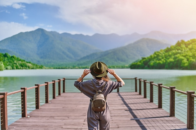 Traveler girl backpacker standing alone on pier and staring at lake and mountains
