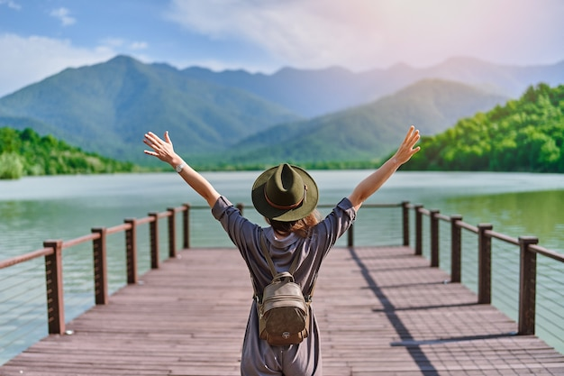 Traveler girl backpacker with open raised arms standing on pier and staring at lake and mountains
