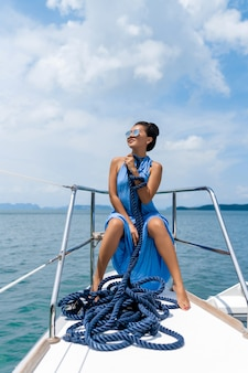 Traveler girl in a blue dress with blue  rope on yacht.