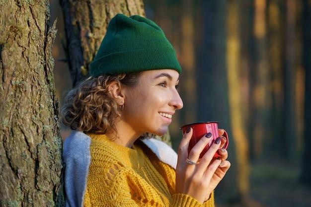 여행자 소녀는 나무에서 금속 머그에서 뜨거운 음료를 마시는 숲속의 젊은 여성 등산객에서 뜨거운 차를 즐깁니다.