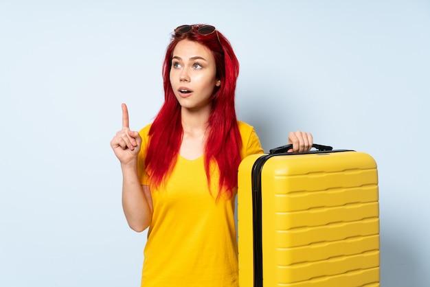 Девушка путешественника держа чемодан изолированный на голубой предпосылке думая идея указывая палец вверх