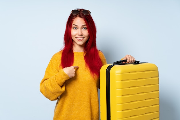 Traveler girl holding a suitcase on blue wall with surprise facial expression