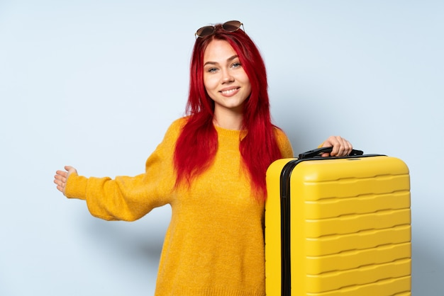 Traveler girl holding a suitcase isolated on blue wall extending hands to the side for inviting to come