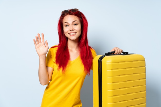 Traveler girl holding a suitcase isolated on blue wall saluting with hand with happy expression