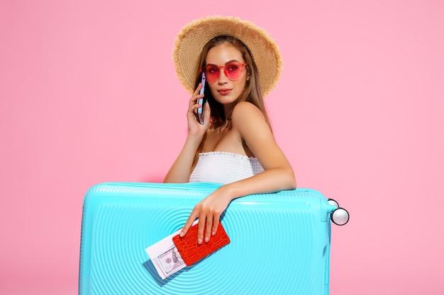 Девушка-путешественница держит деньги на паспортные билеты с чемоданом и вызывает такси в концепцию путешествия в аэропорт