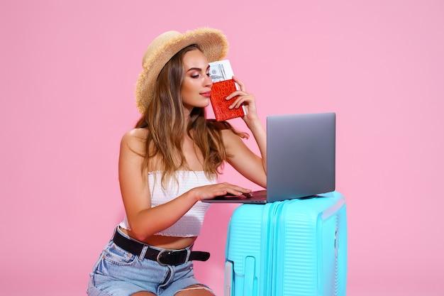 Девушка-путешественница держит деньги на паспортные билеты с чемоданами и использует концепцию путешествий на ноутбуке