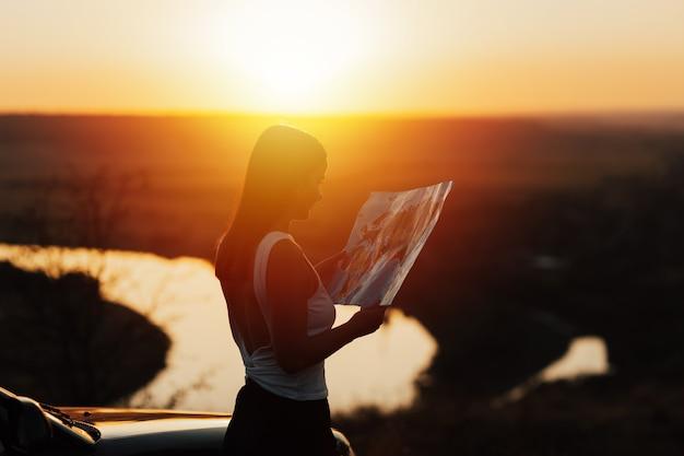 Девушка путешественника смотрит в правильном направлении на карте, ярко-оранжевый свет заката.