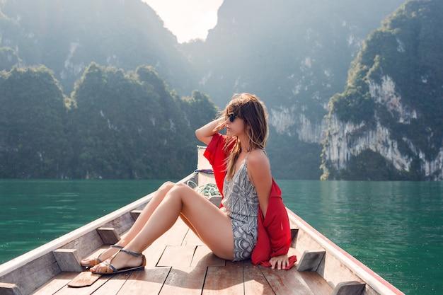Ragazza del viaggiatore che si rilassa sulla barca ed esplora incredibili scogliere tropicali enormi. capelli ventosi, estasi, libertà. thailandia, asia.