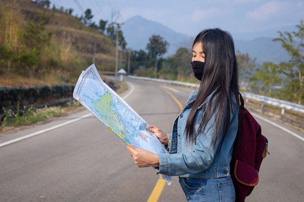 Traveler girl searching right direction on map