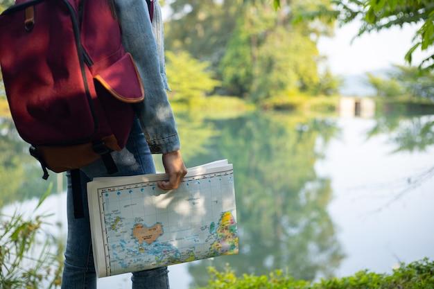 Ragazza viaggiatrice che cerca la giusta direzione sulla mappa