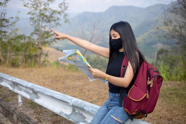 Путешественник девушка ищет правильное направление на карте