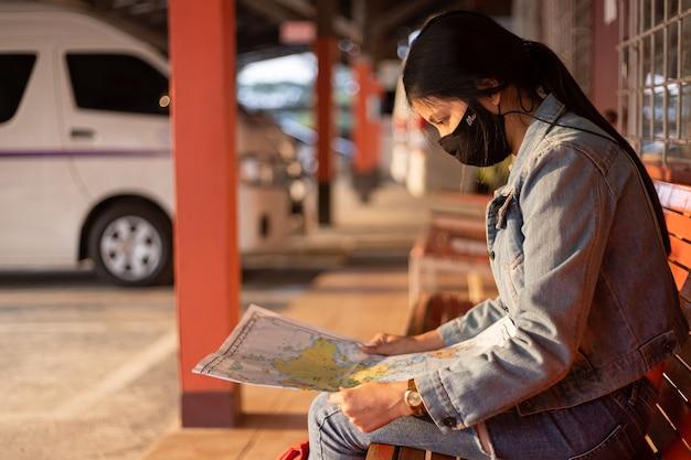 地図上で正しい方向を探す旅行者の女の子