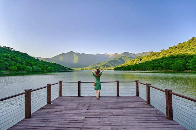 Traveler girl standing alone on edge of pier and staring at lake. beautiful freedom moment and serene quiet peaceful atmosphere in nature. back view