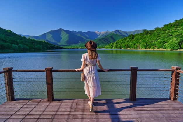 Traveler girl standing alone on edge of pier and staring at lake and mountains. enjoying beautiful freedom moment life and serene quiet peaceful atmosphere in nature. back view