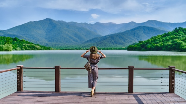 Traveler girl standing alone on edge of pier and staring at lake and mountains. enjoying happy freedom moment life and serene quiet peaceful atmosphere in nature. back view