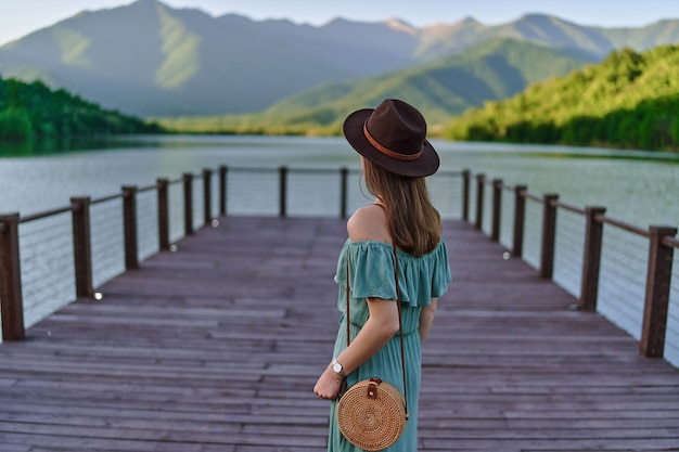 Traveler girl standing alone on pier and staring at lake and mountains. beautiful freedom moment and serene peaceful atmosphere in nature. back view