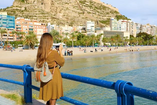アリカンテ、スペインのプラヤデルポスティゲの写真を撮る旅行者の女の子