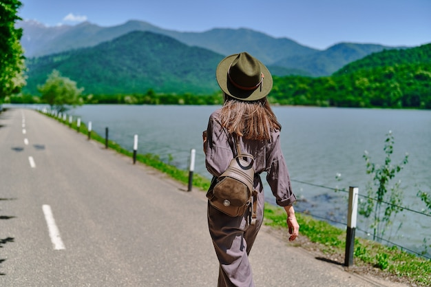 Traveler girl wearing felt hat and backpack walking alone on a road with lake and mountains view. enjoying beautiful freedom moment life and serene quiet peaceful calm atmosphere in nature. back view