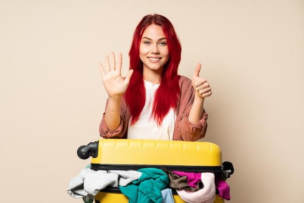 指で6を数えるベージュ色の背景に分離された服の完全なスーツケースを持つ旅行者の女の子