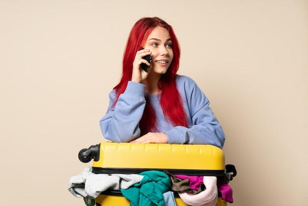 Девушка-путешественница с полным чемоданом одежды на бежевом фоне ведет разговор с кем-то по мобильному телефону