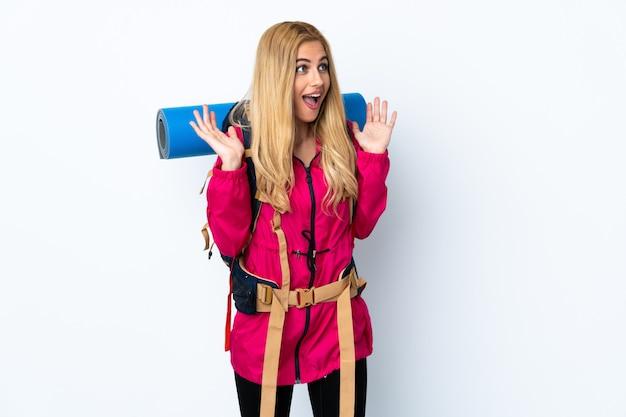 努力をしたため腰痛に苦しんでいるベージュの壁に分離された服の完全なスーツケースを持つ旅行者の女の子