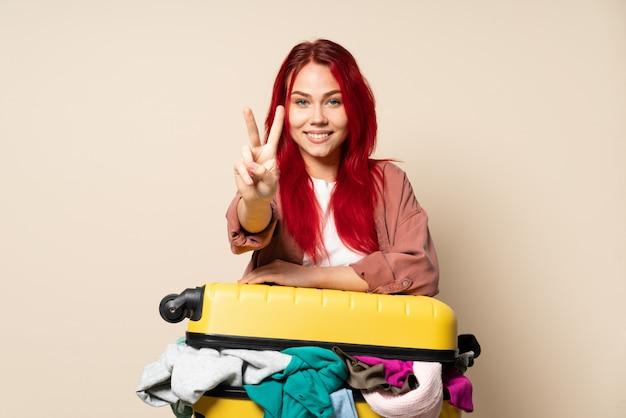 ベージュの壁の笑顔と勝利のサインを示す服でいっぱいのスーツケースを持つ旅行者の女の子