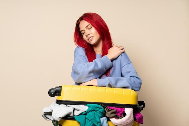 Путешественница с полным чемоданом одежды на бежевой стене страдает от боли в плече из-за усилий