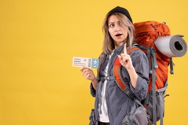 Девушка-путешественница с рюкзаком держит билет на самолет, удивляя своей идеей