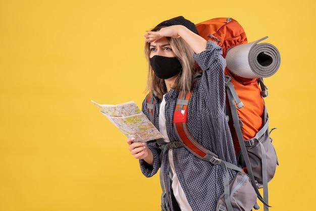 黒いマスクと何かを見ている地図を持ったバックパックを持つ旅行者の女の子
