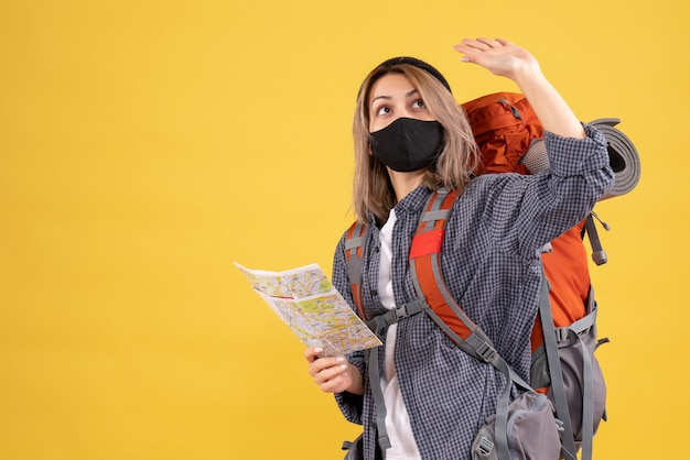 黒いマスクと地図を見上げるバックパックを持つ旅行者の女の子