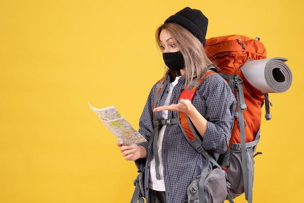 黒いマスクとバックパックを持った旅行者の女の子が地図を見て