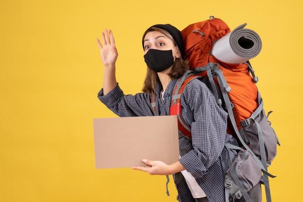Ragazza viaggiatrice con maschera nera e zaino con cartone che saluta qualcuno