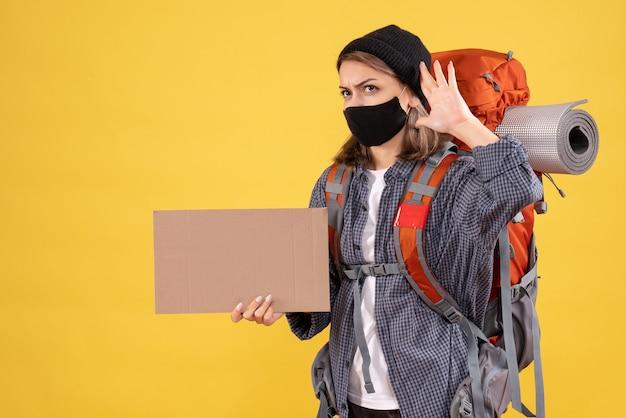 Ragazza viaggiatrice con maschera nera e zaino in possesso di cartone che ascolta qualcosa