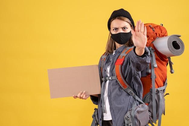 Ragazza viaggiatrice con maschera nera e zaino in possesso di cartone che fa il segnale di stop