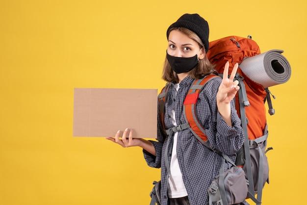 Ragazza viaggiatrice con maschera nera e zaino in possesso di cartone che fa segno di vittoria