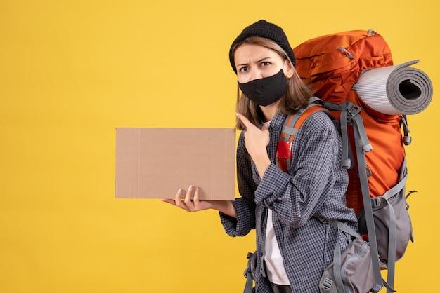 Ragazza viaggiatrice con maschera nera e zaino con cartone