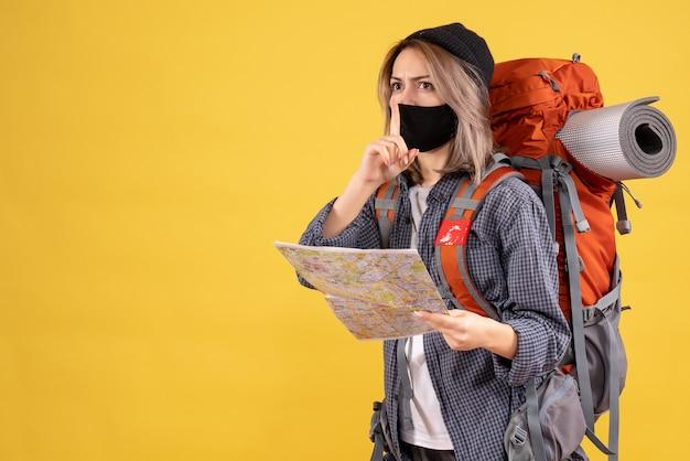 Ragazza viaggiatrice con maschera nera e zaino con in mano una mappa che fa il segno del silenzio