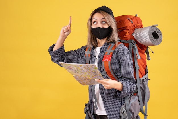 Traveler girl with black mask and backpack holding map pointing finger up