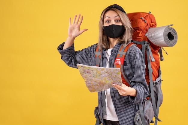 Ragazza viaggiatrice con maschera nera e zaino che tiene la mappa agitando la mano