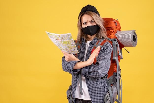 Ragazza viaggiatrice con maschera nera e zaino con mappa