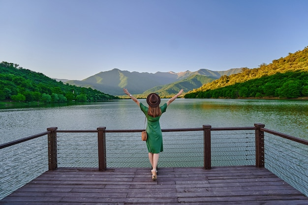 橋脚の端に一人で立って、湖と山を見つめている開いた上げられた腕を持つ旅行者の女の子