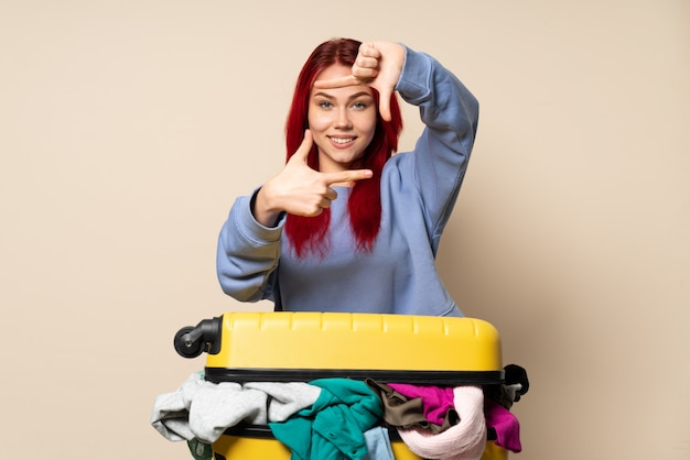 Traveler girl with a suitcase full of clothes on beige wall focusing face. framing symbol