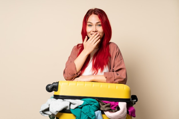 Traveler girl with a suitcase full of clothes on beige wall happy and smiling covering mouth with hand