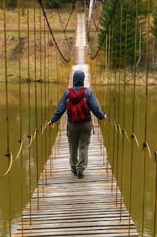旅行者は春の川に架かる吊り橋に沿って行きます