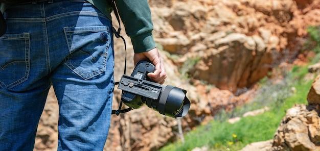 Traveler hand photo camera in rock wall